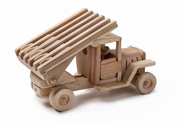 Caminhão militar de brinquedo de madeira feito à mão isolado no branco com muito espaço vazio para mensagem.