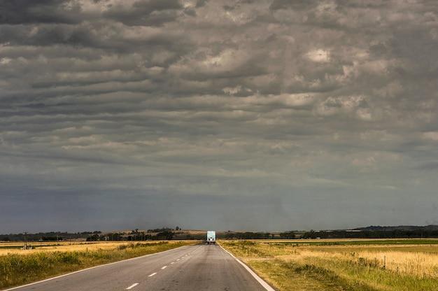Caminhão na estrada cercada por campos vazios sob o céu nublado