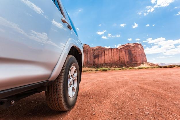 Caminhão no deserto com montanhas ao fundo.