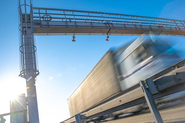 Caminhão passando através de um portão de pedágio em uma rodovia com pedágio