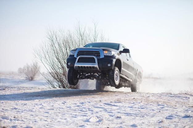 Caminhão preto viajando na neve e pulando