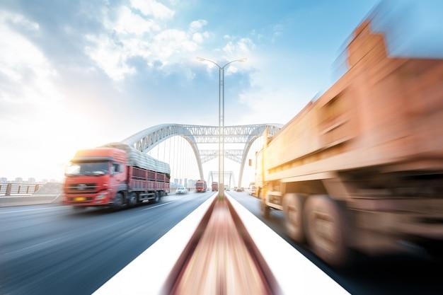 Caminhão que apressa-se através de uma ponte no por do sol, borrão de movimento.
