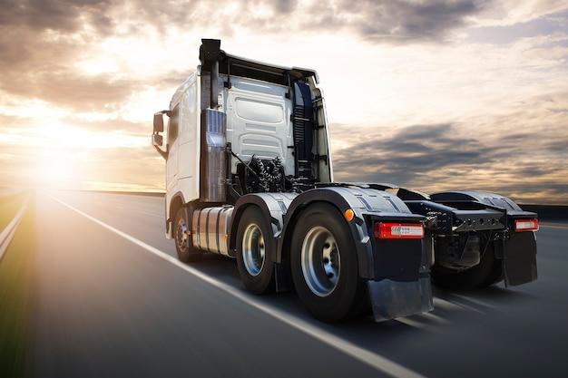 Caminhão semi-caminhão dirigindo na estrada da estrada ao pôr do sol conceito de transporte logístico de caminhão de carga de estrada de céu