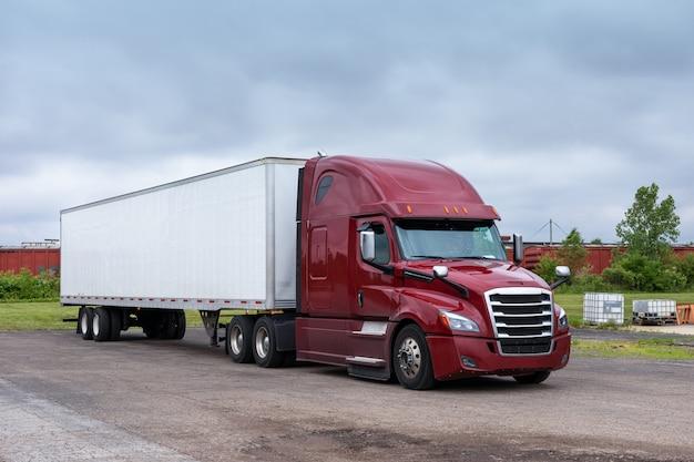 Caminhão semi moderno de plataforma grande para transporte longo com cabine alta para melhorar as características aerodinâmicas transportando um semi-reboque van seco com carga comercial na estrada.