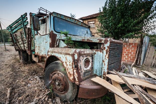 Caminhão velho abandonado em frente a uma parede quintal de aldeia