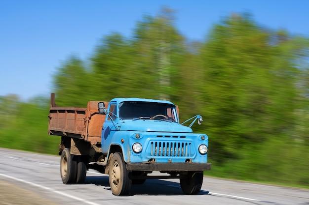 Caminhão velho azul correndo na estrada