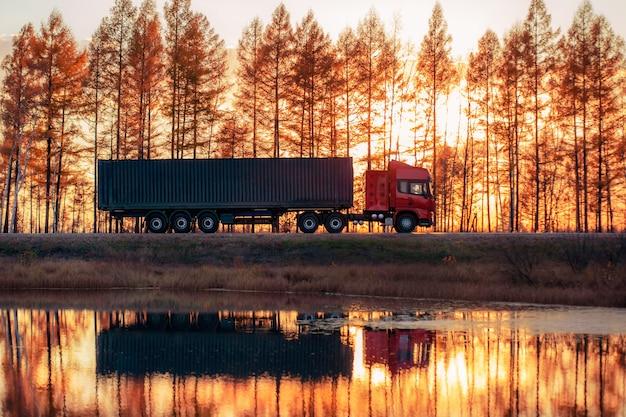 Caminhão vermelho em uma estrada ao pôr do sol. foco no contêiner