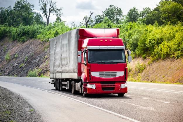 Caminhão vermelho passando por uma estrada com alguma carga