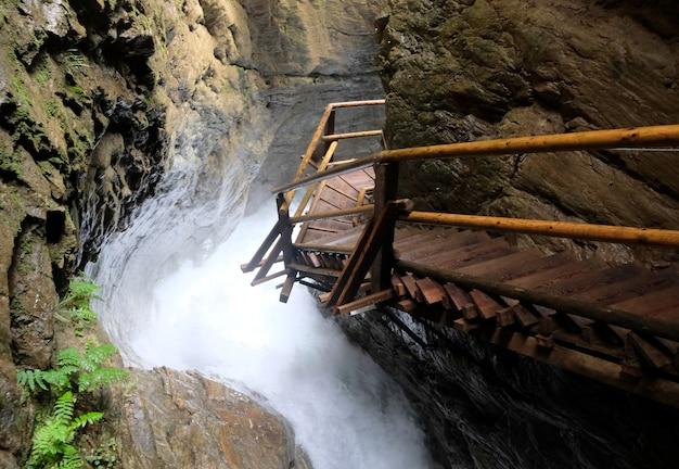 Caminho a pé de madeira como ponte sobre a cascata