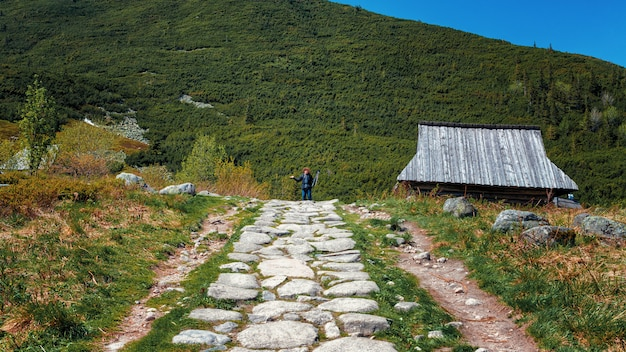 Caminho chapado branco no vale verde da montanha e fotógrafo longe