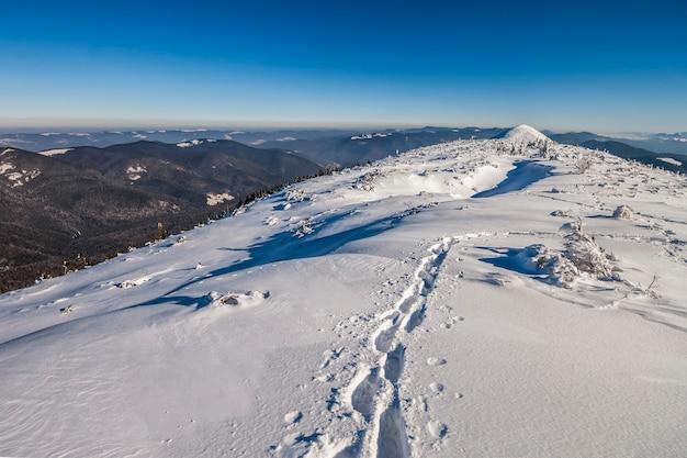 Caminho com pegadas na neve nas montanhas de inverno.
