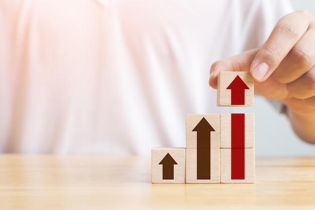 Caminho de carreira de escada para o conceito de processo de sucesso de crescimento de negócios. mão, organizando o bloco de madeira, empilhando como degrau com seta para cima