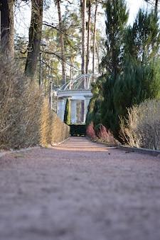 Caminho de cascalho entre os arbustos em perspectiva para o gazebo de pedra no parque