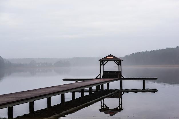 Caminho de madeira acima da água, cercado por árvores com um fundo nebuloso