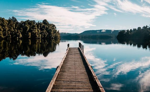 Caminho de madeira com árvores e um céu azul refletido no lago mapourika waiho na nova zelândia