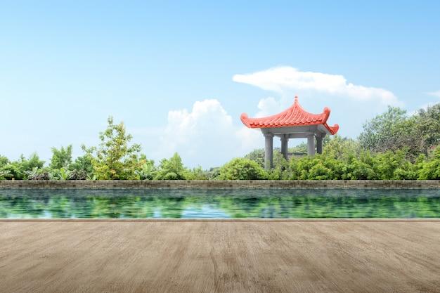 Caminho de madeira com gazebo chinês edifício com lago e árvores