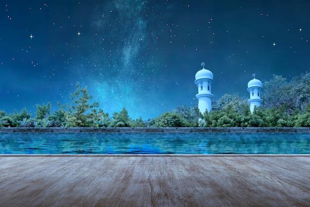 Caminho de madeira com o minarete da mesquita com lago e árvores à noite