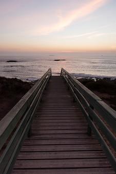 Caminho de madeira para o mar enquanto pôr do sol com barcos no fundo