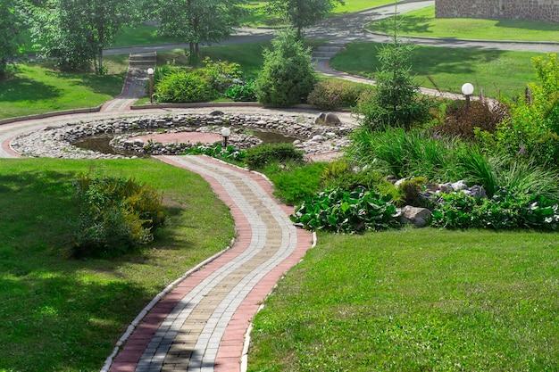 Caminho de paralelepípedos no parque e lagoa decorativa. conceito de design de paisagem.