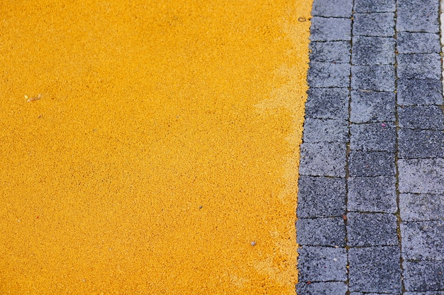 Caminho de paralelepípedos perto de pequenas rochas amarelas