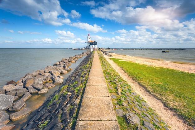 Caminho de pedra levando ao farol na costa do mar no fundo do céu azul com nuvens ao pôr do sol na primavera na holanda. paisagem com trilha, pedras, grama, praia, mar e farol. natureza