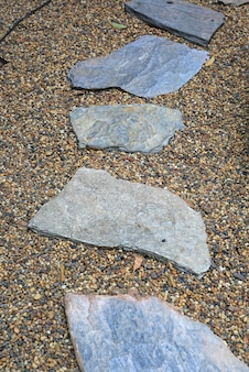 Caminho de pedra no parque com fundo do seixo.