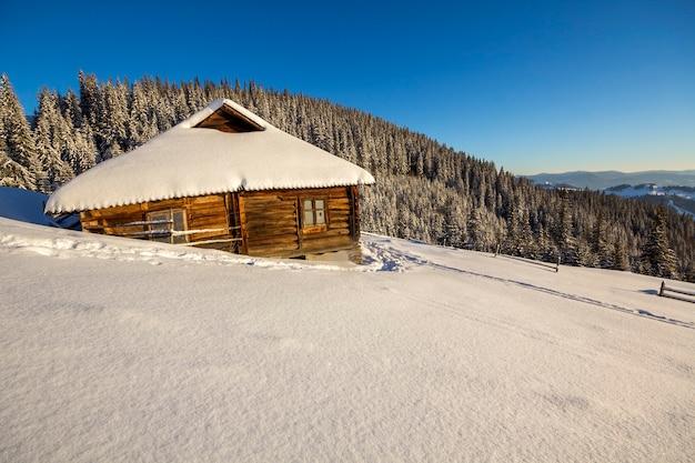 Caminho de pegadas humanas em neve branca e profunda levando a uma pequena cabana de pastor de madeira abandonada