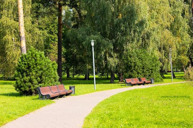 Caminho do parque com bancos, grama verde e árvores.