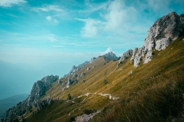 Caminho em uma colina no meio de um campo gramado com falésias rochosas, com um céu azul
