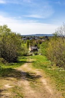 Caminho estreito em um terreno verde cercado por muitas árvores com casas