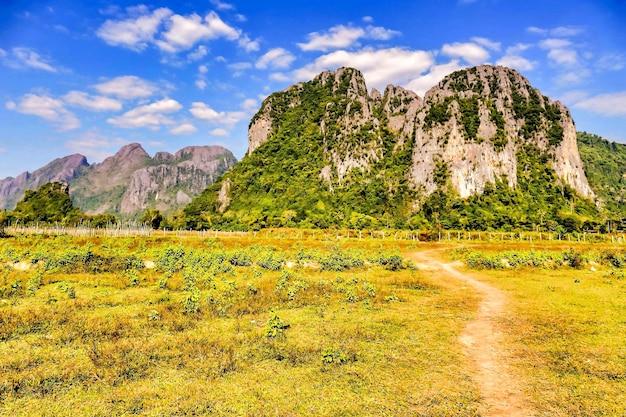 Caminho no meio do campo com montanhas ao longe