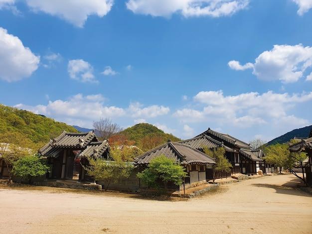Caminho no meio dos edifícios de uma vila coreana sob um céu azul