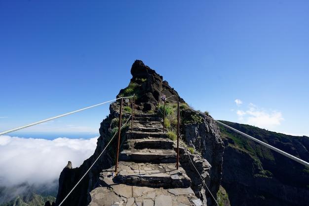 Caminho rochoso em direção a um topo de montanha com céu claro ao fundo