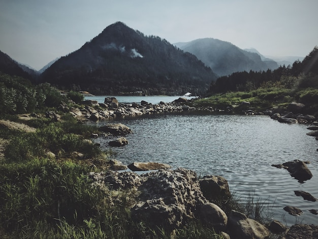 Caminho rochoso no meio da água com uma montanha ao fundo