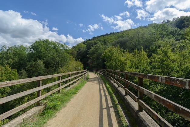 Caminho rural através de uma ponte e suas cercas