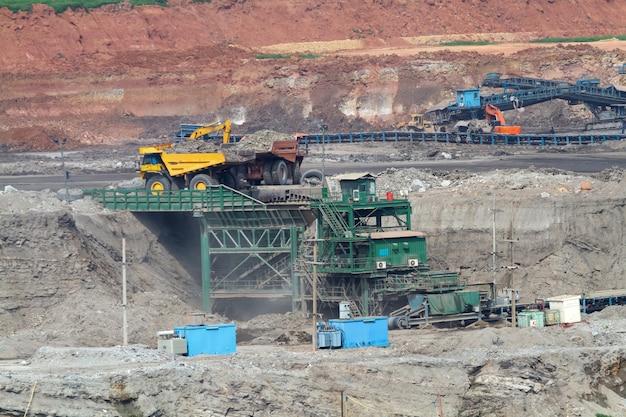 Caminhões carregando minério despejado na máquina