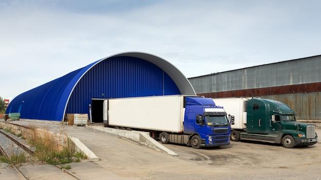 Caminhões carregando na instalação na área de carregamento.