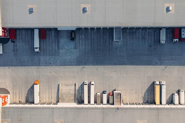 Caminhões com reboques aguardam carregamento de mercadorias para transporte na aeria entreposto de carga ...