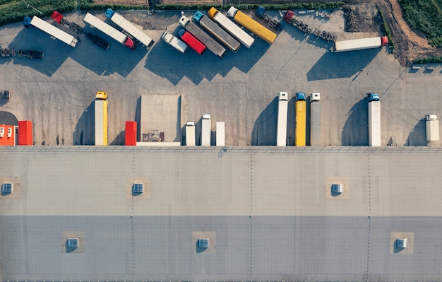 Caminhões com reboques são carregados e descarregados no terminal de carga pela manhã, top vu airive shot ...