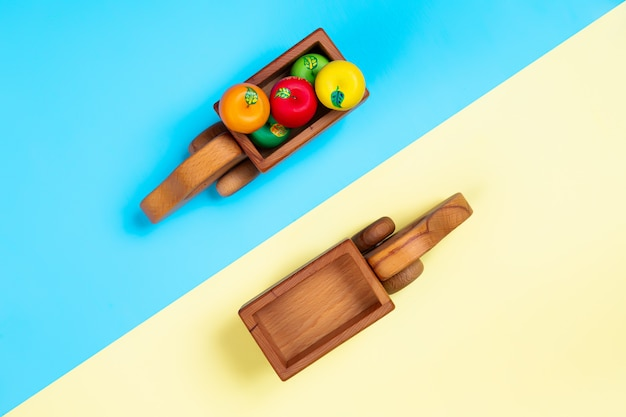 Caminhões de brinquedo de madeira com maçãs no fundo isolado