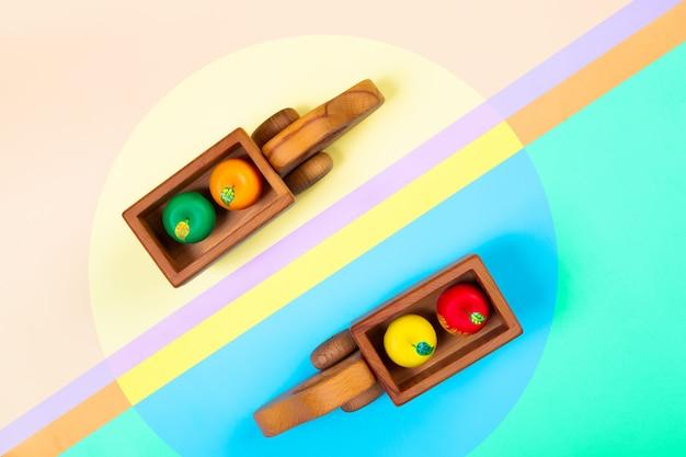 Caminhões de brinquedos de madeira com maçãs em um fundo geométrico vibrante multicolorido isolado.