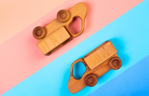 Caminhões de brinquedos de madeira no fundo geométrico vibrante multicolorido isolado.