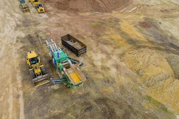 Caminhões e máquinas pesadas limpando o terreno para a construção