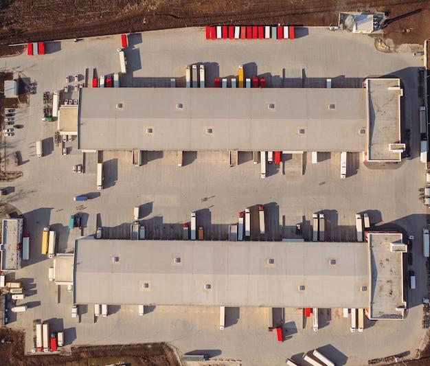 Caminhões esperando para serem carregados no terminal de carga na vista superior da manhã de verão