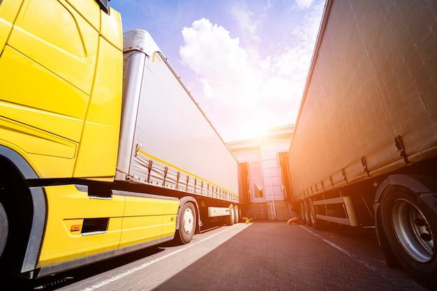 Caminhões grandes perto do armazém contra o fundo do céu azul