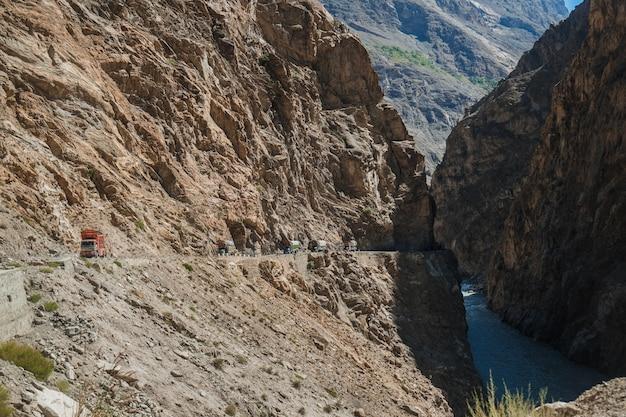 Caminhões paquistaneses que viajam na estrada pavimentada ao longo da montanha perto do penhasco na estrada de karakoram.