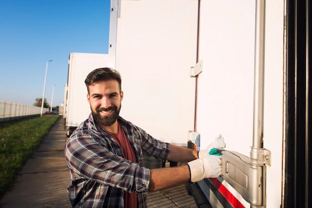 Caminhoneiro com luvas de trabalho abrindo ou fechando as portas traseiras do trailer do caminhão verificando as mercadorias para transporte.