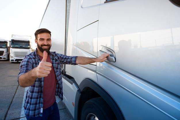 Caminhoneiro profissional barbudo de meia-idade parado ao lado de seu caminhão com o polegar para cima