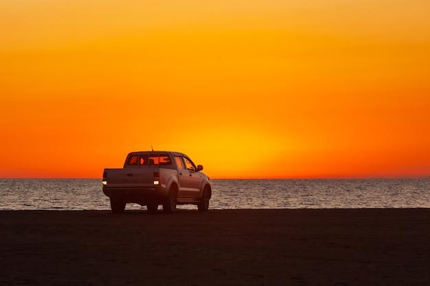 Caminhonete estacionada em frente ao mar negro ao pôr do sol. natureza.