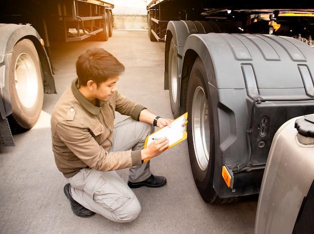 Camionista asiático que guarda a prancheta que inspeciona a lista de verificação da manutenção do veículo da segurança rodas e pneu de um caminhão.